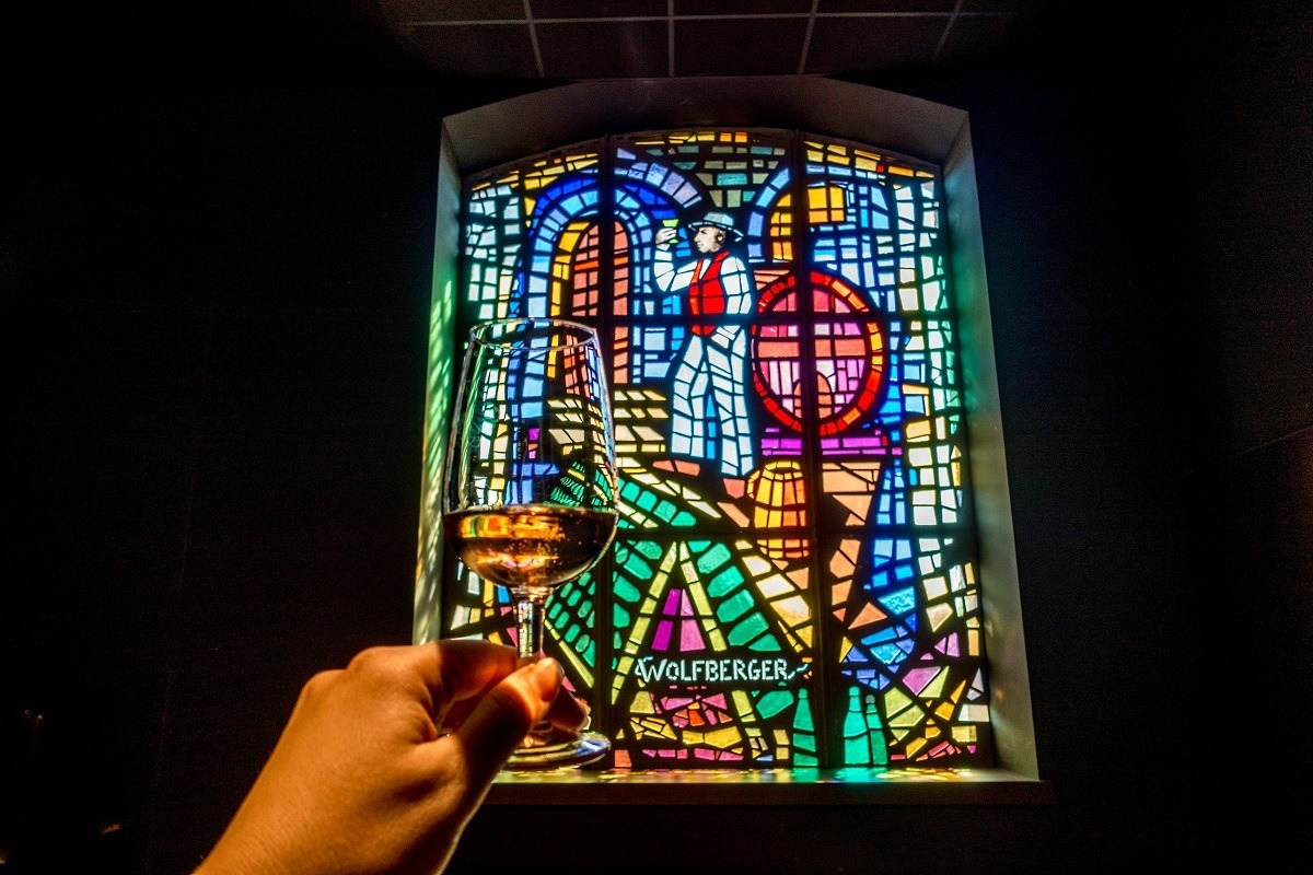 Wine glass and stained glass window at Wolfberger winery on the Alsace wine route
