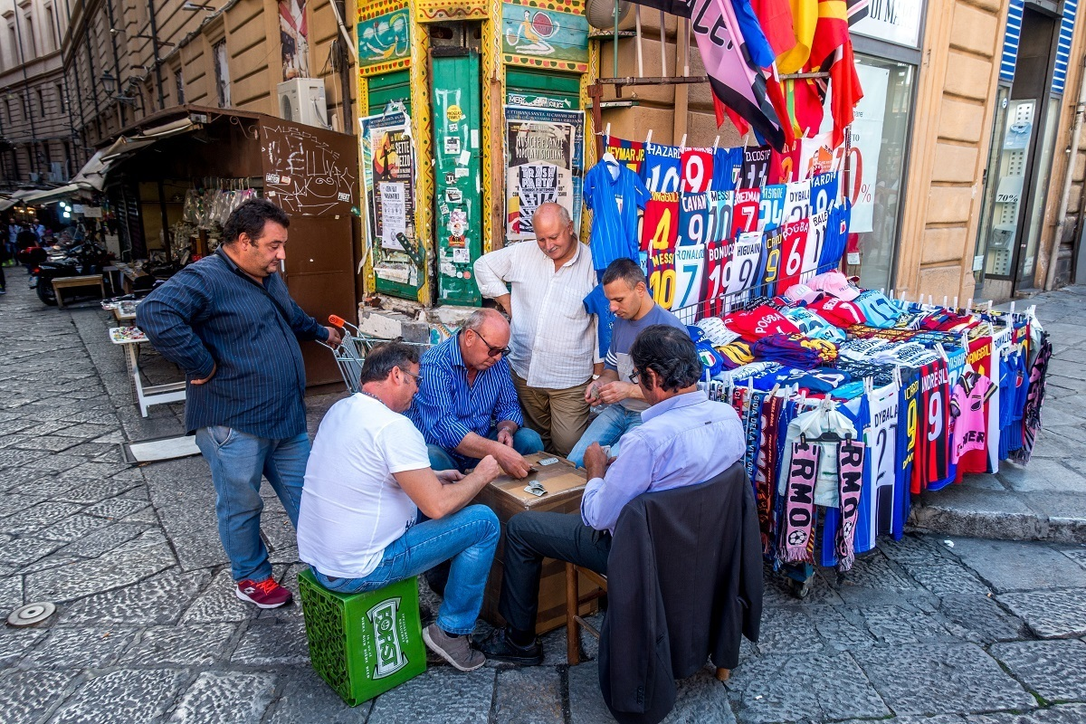 Men playing cards in an outdoor market