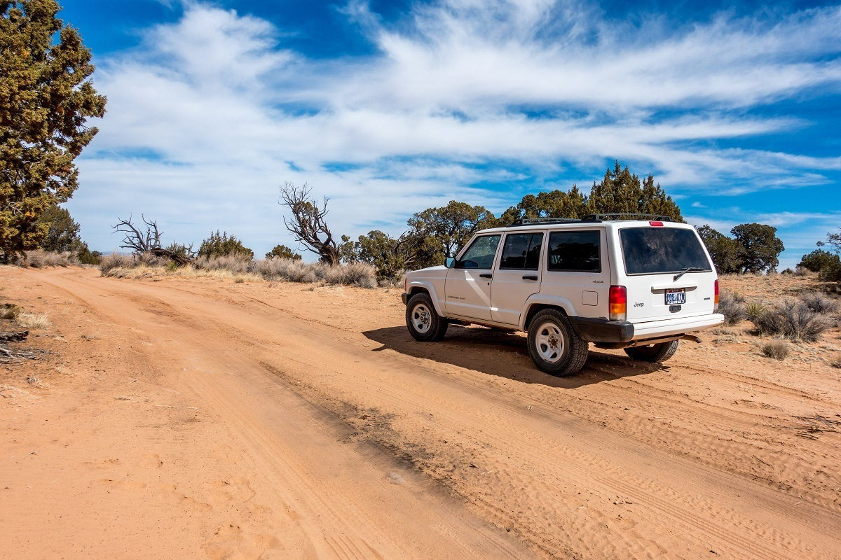 A white 4x4 jeep rental car on the sandy road to White Pocket
