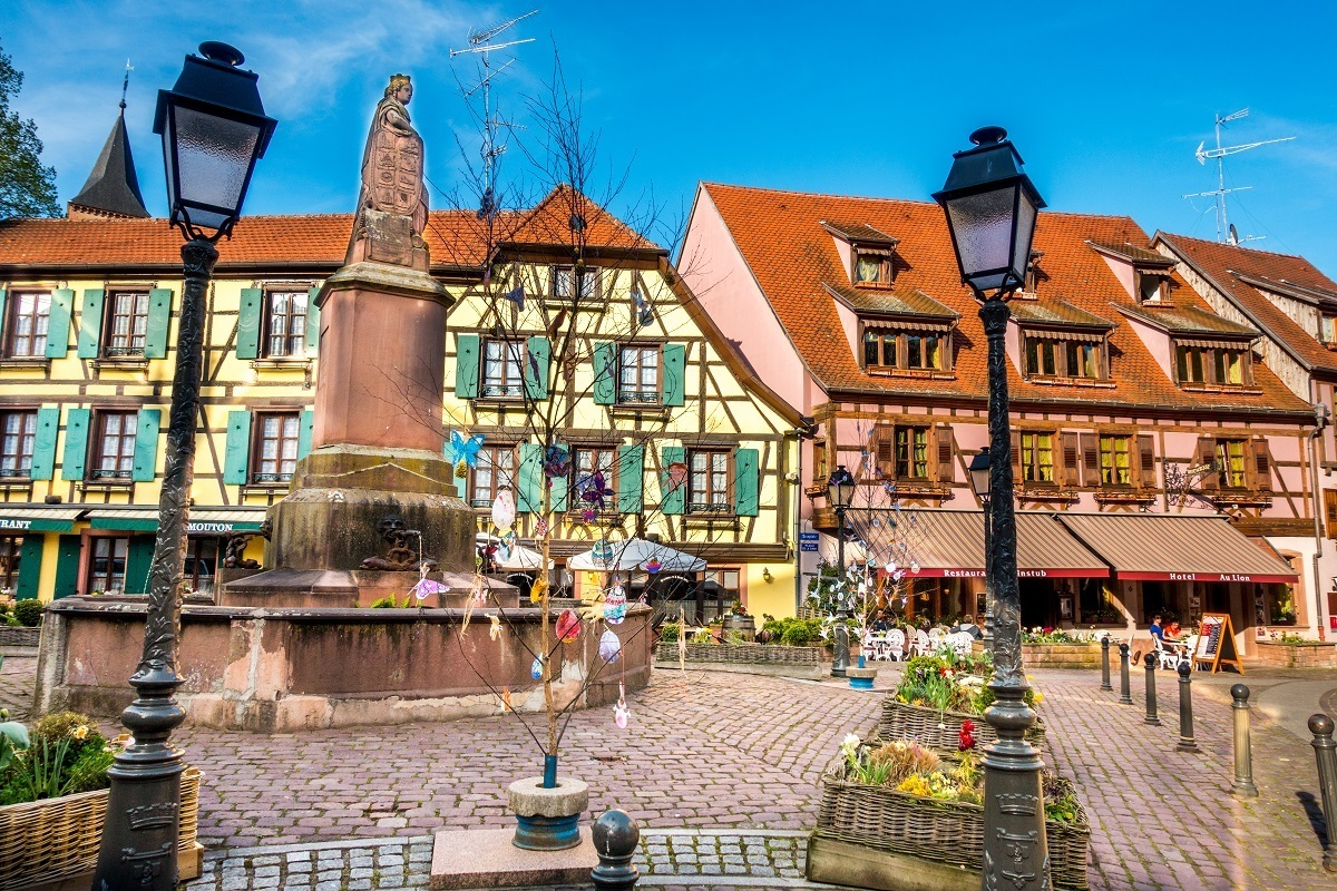 Fountain and buildings in Ribeauville, a fun stop on the Route des Vins d'Alsace