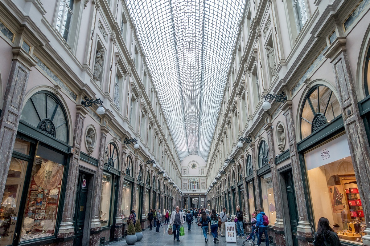 People walking through gallery of indoor shops