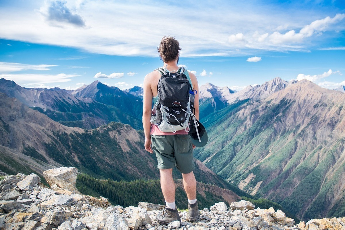 Person hiking on a rocky trail looking out at the mountains and a valley