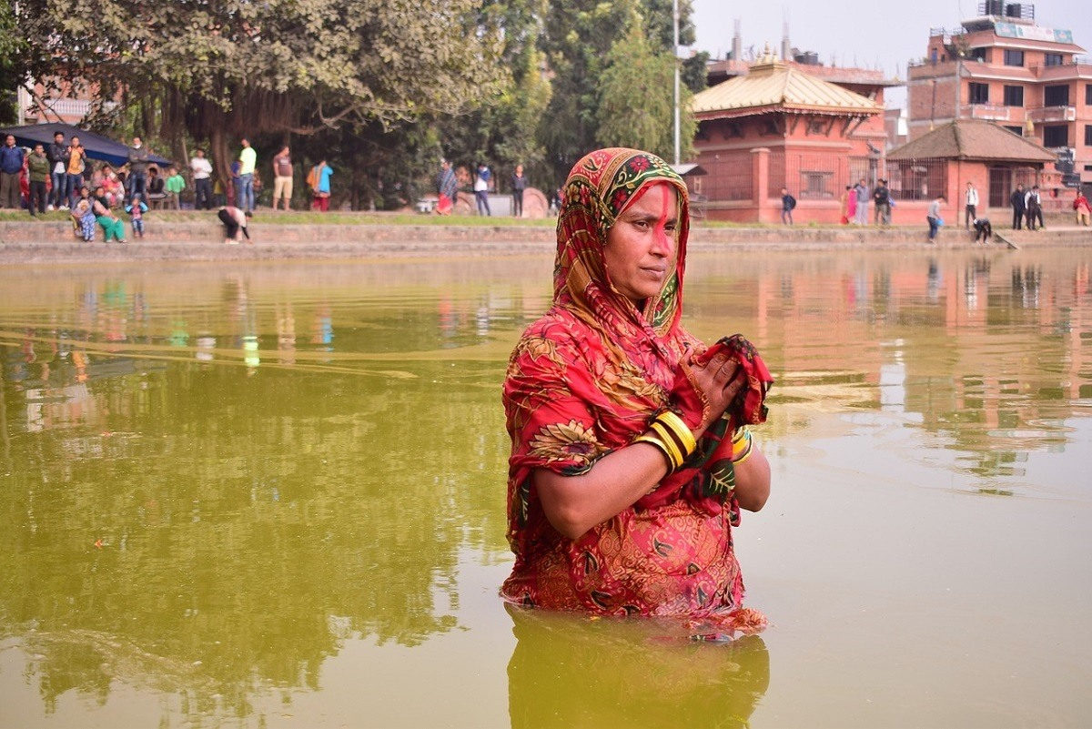 A woman standing up to her waist in a river in India praying
