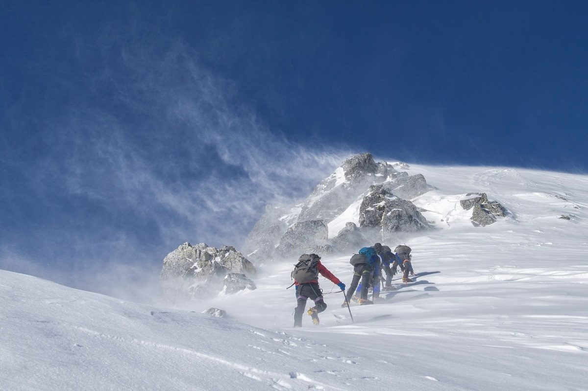 Group of people mountaineering up a steep, snowy mountain
