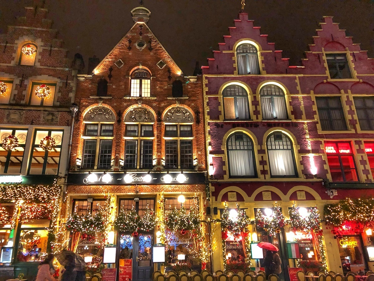 Restaurants at night lit up for Christmas on the main square of the Bruges Christmas market