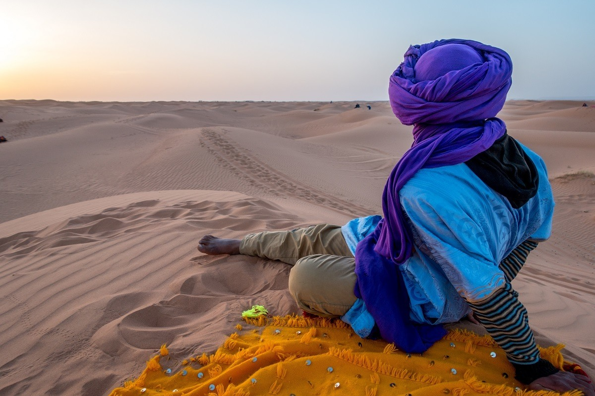 Man looking out over sand dunes