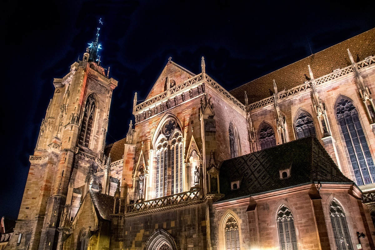 The red stone Collegiate Church of St. Martin lit up at night