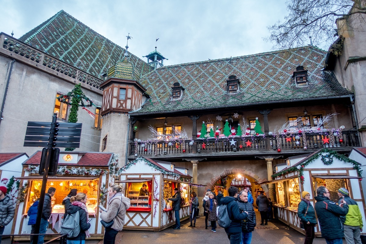 People shopping at market stalls by a building with green tile roof