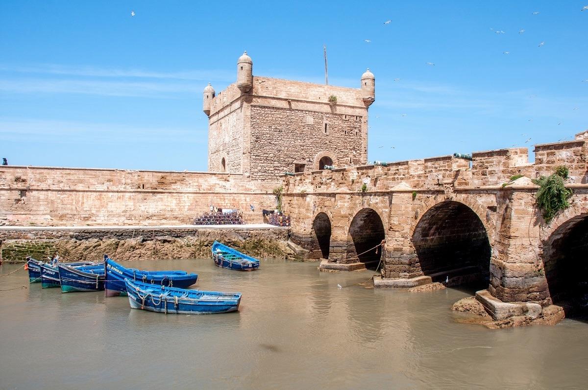Blue fishing boats beside a stone bridge and city wall