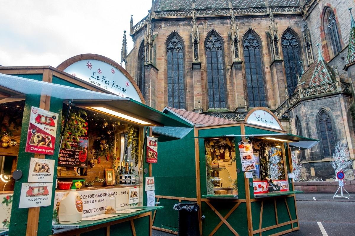 Gourmet food market vendors in green kiosks