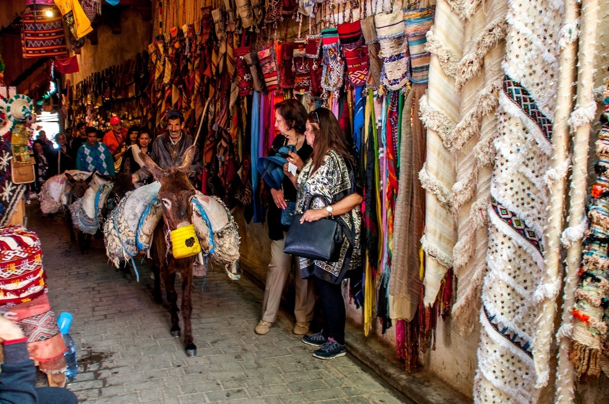 Donkey carrying goods through a market