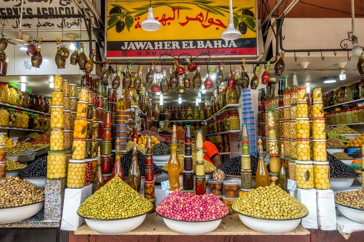 Piles and jars of olives for sale