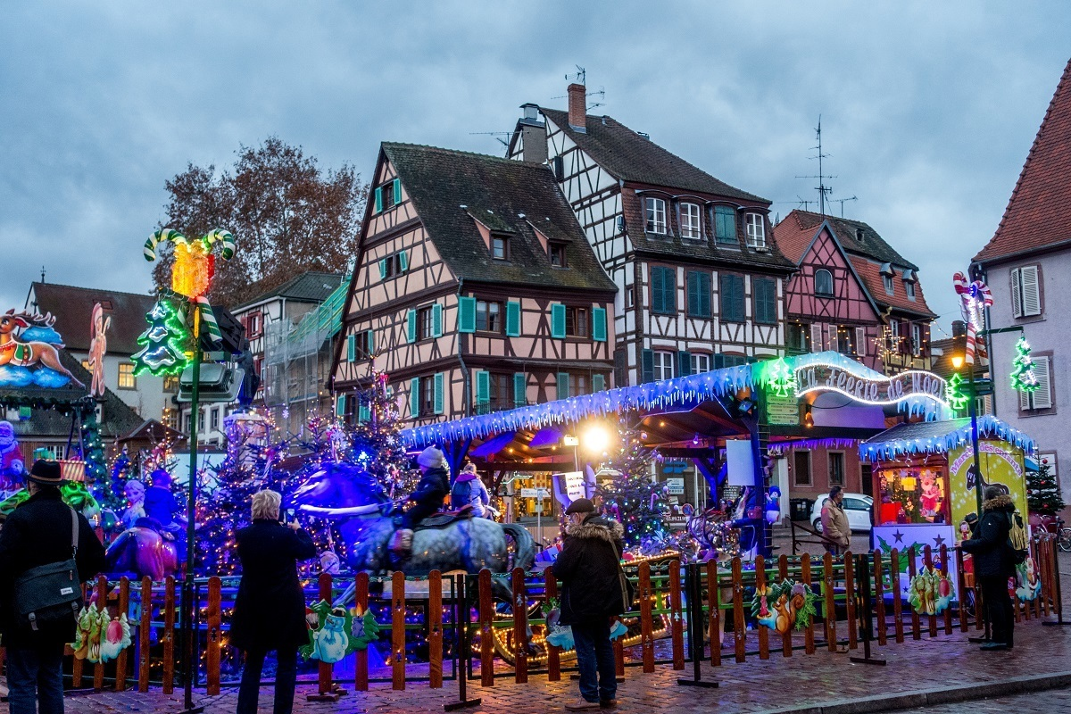 Carnival rides beside half-timbered buildings