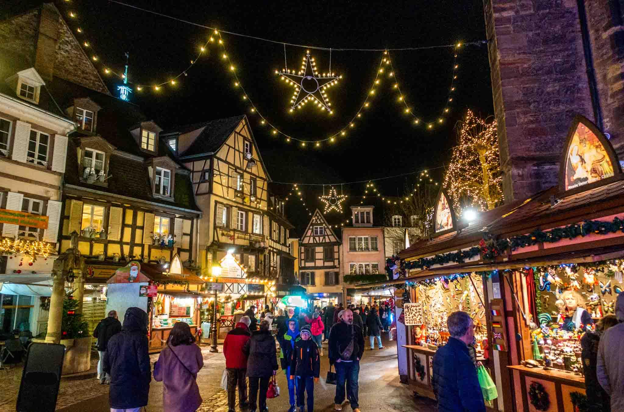 People shopping at stalls at the Colmar Christmas market at night