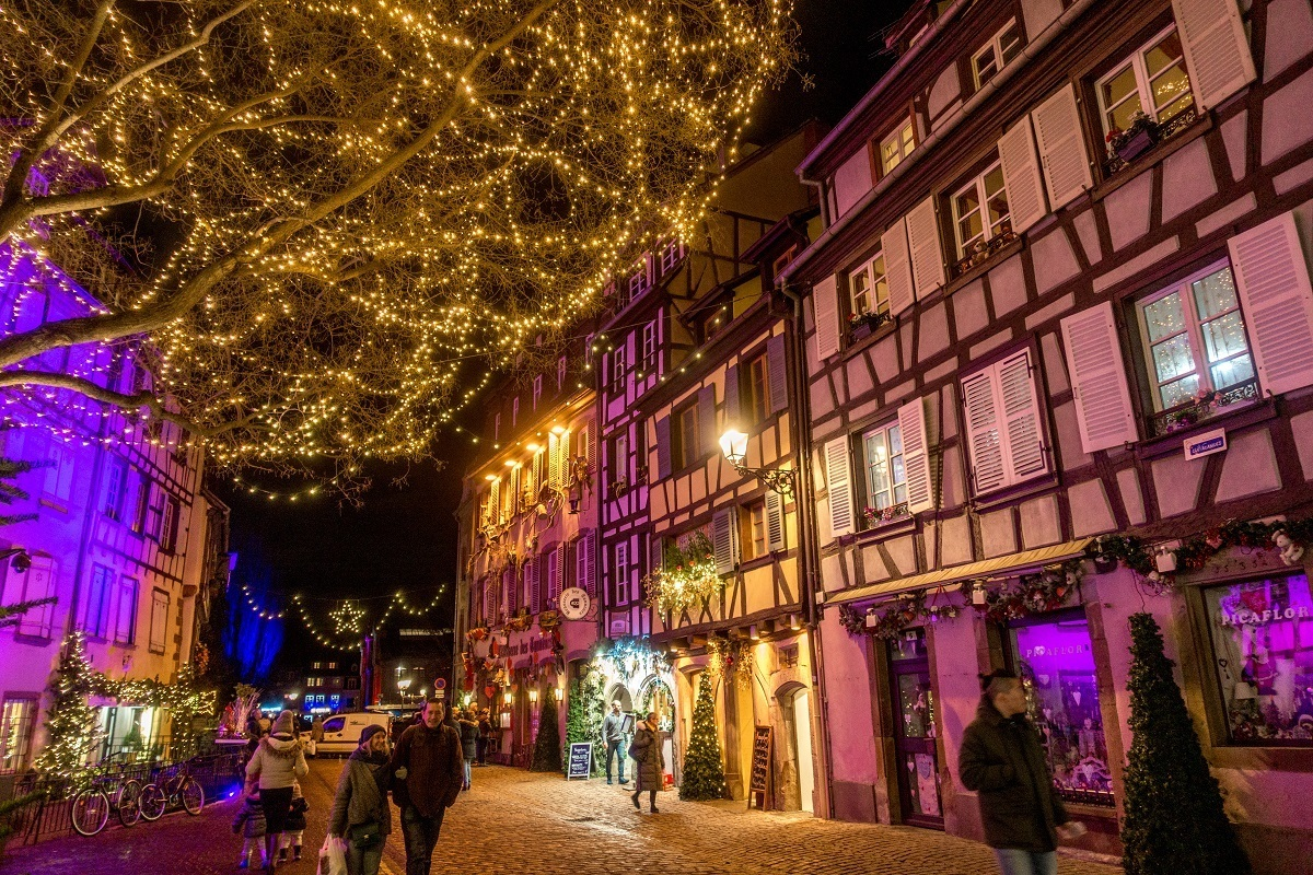 People walking down a street lined with Christmas lights and decorations