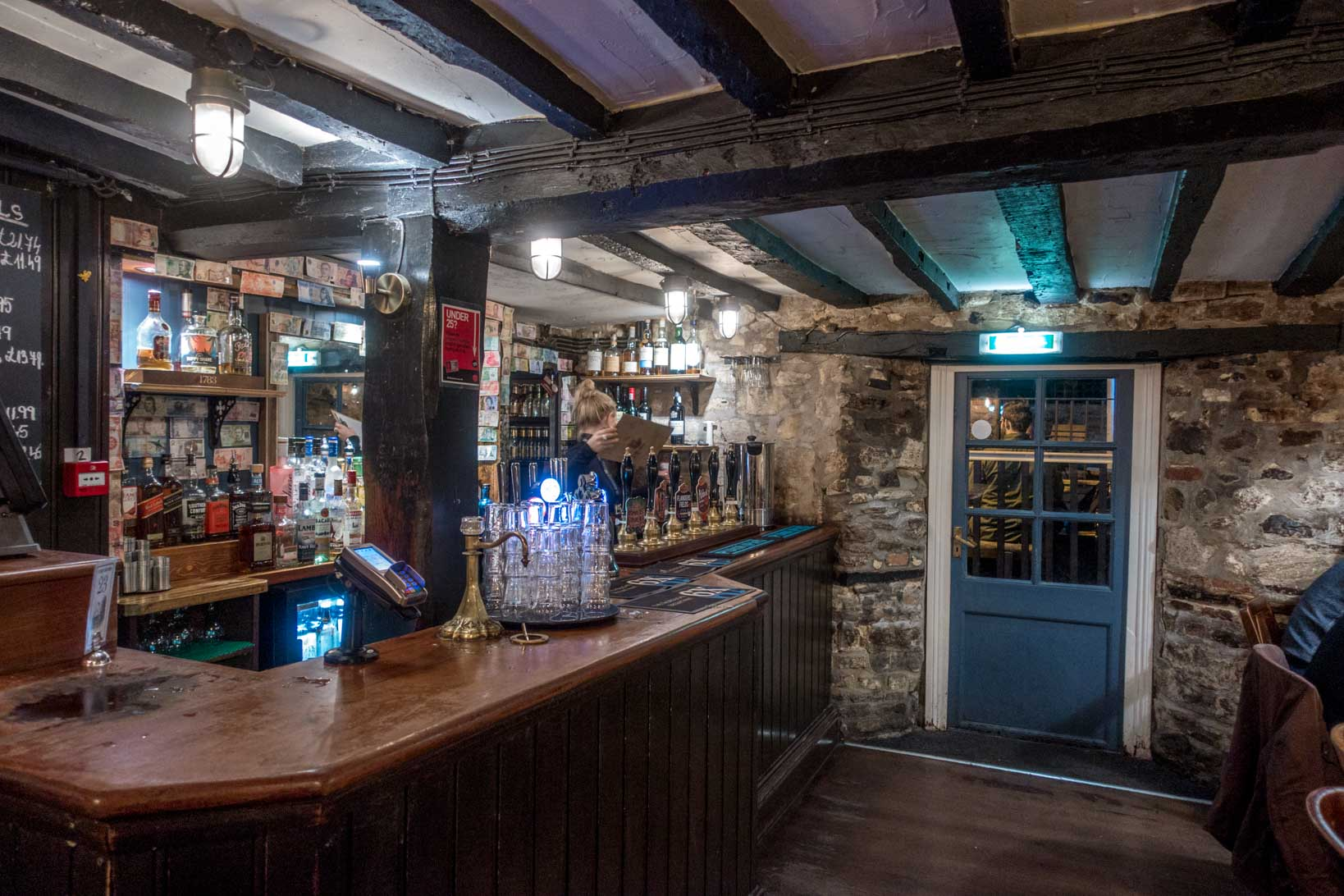 Bar, stone walls, and old wooden beams inside an historic pub