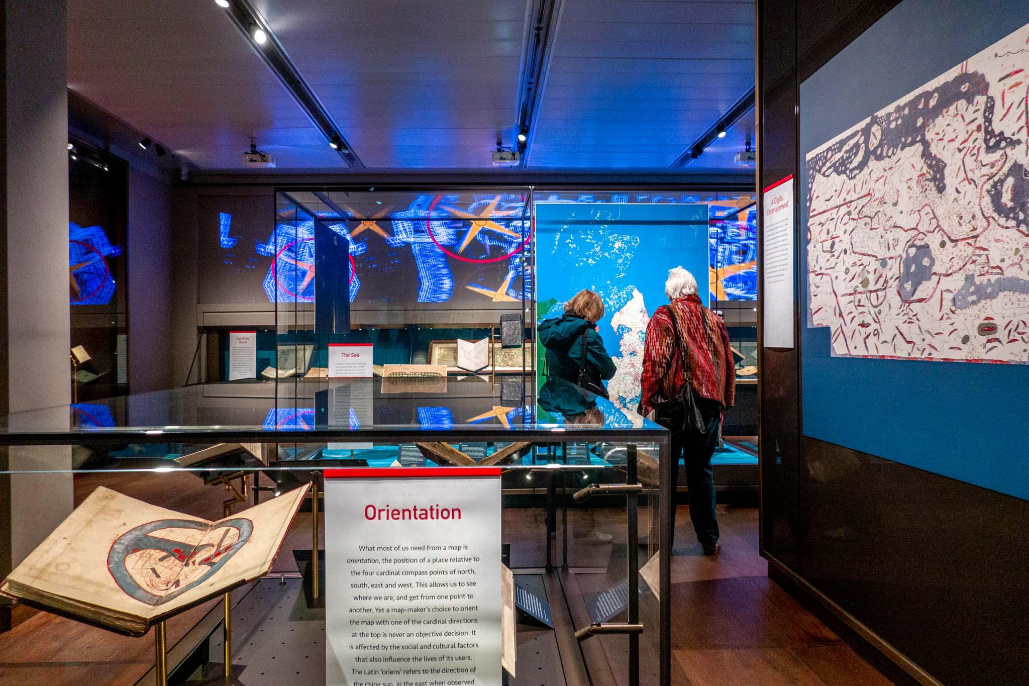 People reading display panels in exhibit rooms