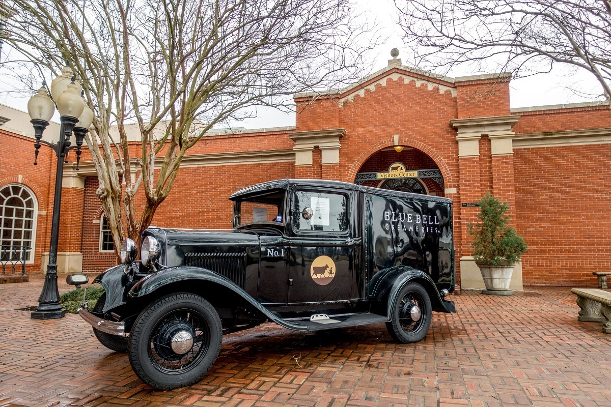 Antique car in front of brick building, Blue Bell ice cream factory