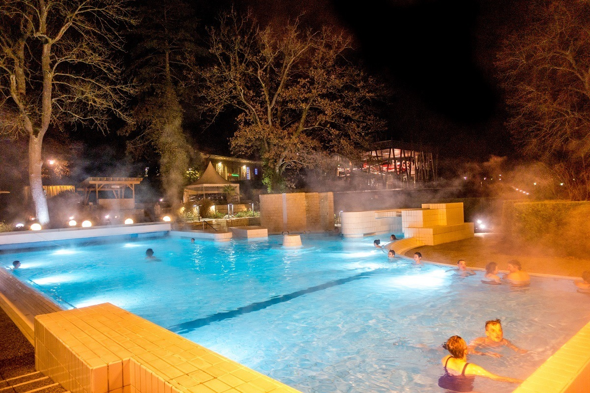 People in heated pools at night