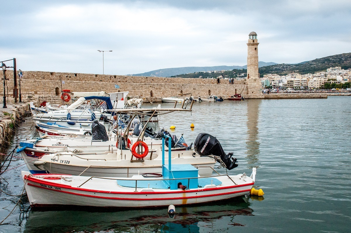 Boats in the harbor along a stone wall