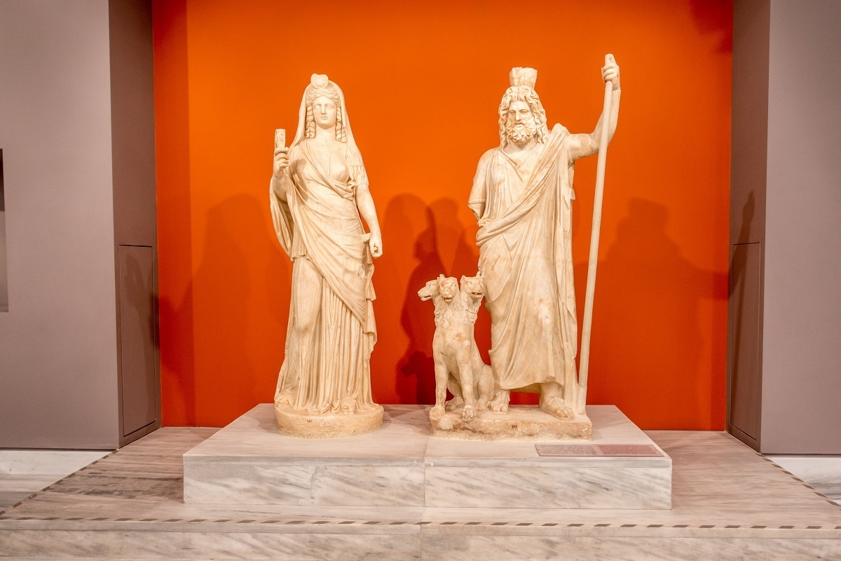 Marble statues of a man, a woman, and a 3-headed dog