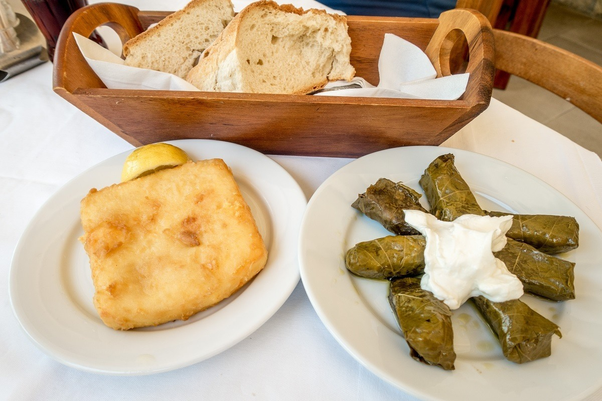Stuffed grape leaves, fried saganaki cheese, and bread on table