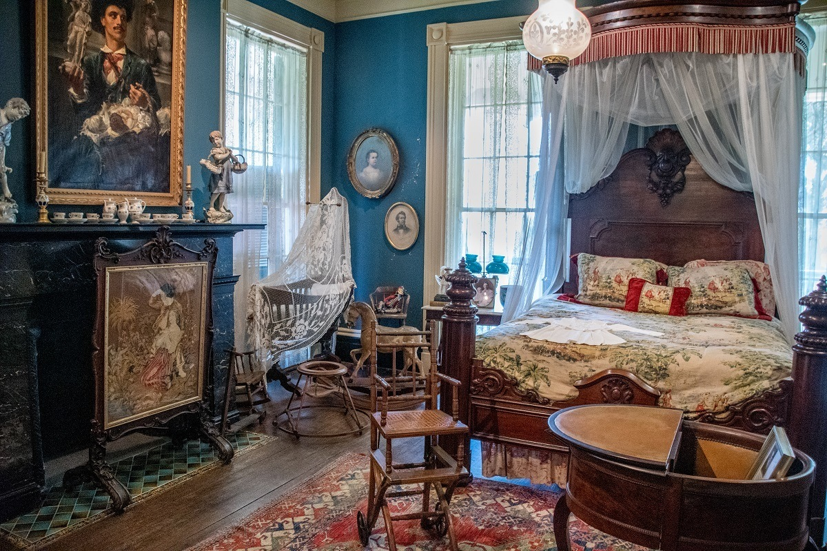 Blue bedroom with portraits on walls