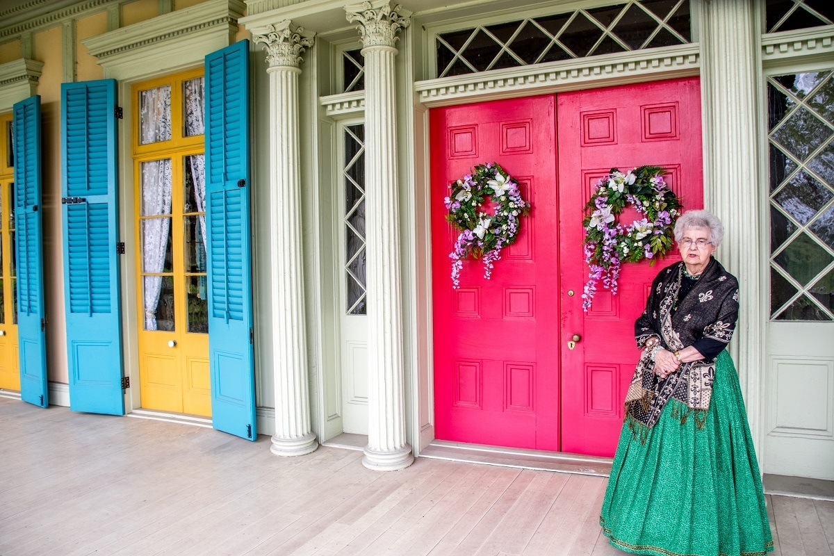 Guide in period dress outside a pink door