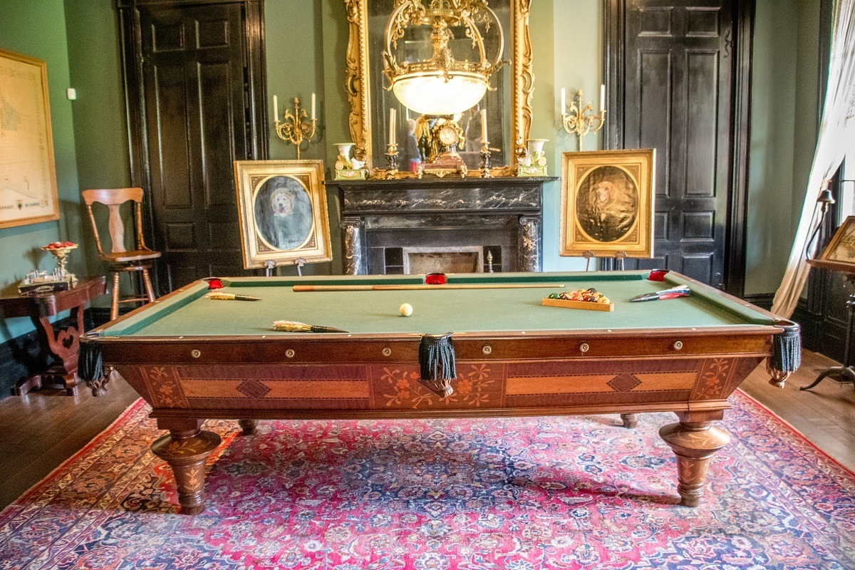 Portraits of dogs flank a pool table