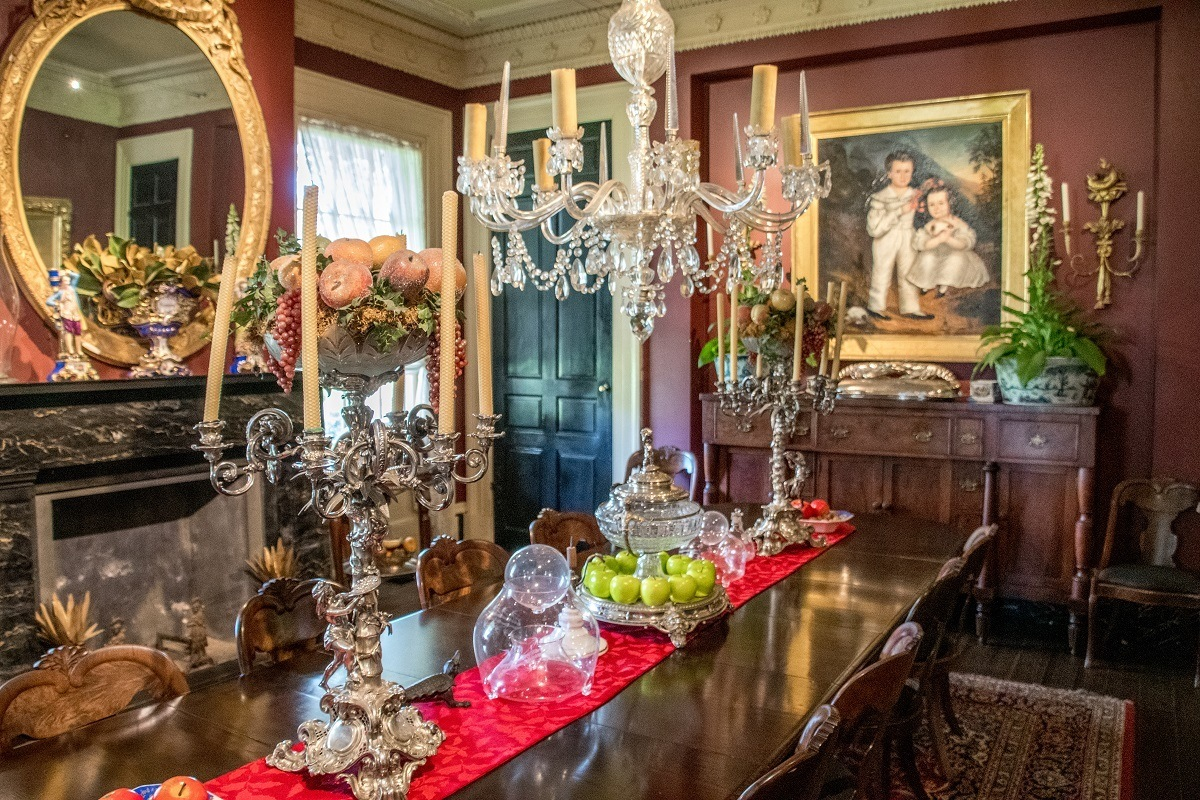 Dining room with paintings, chandeliers, and candelabras