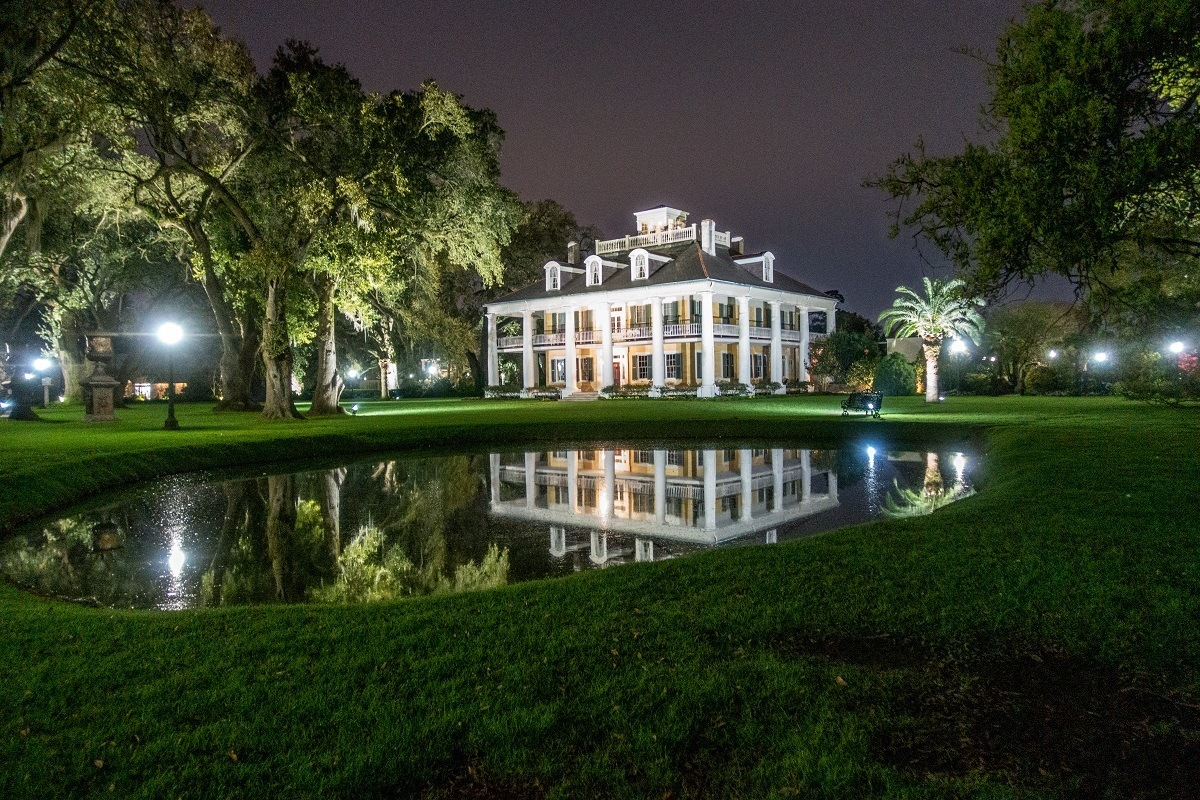 White mansion lit up at night beside a pond