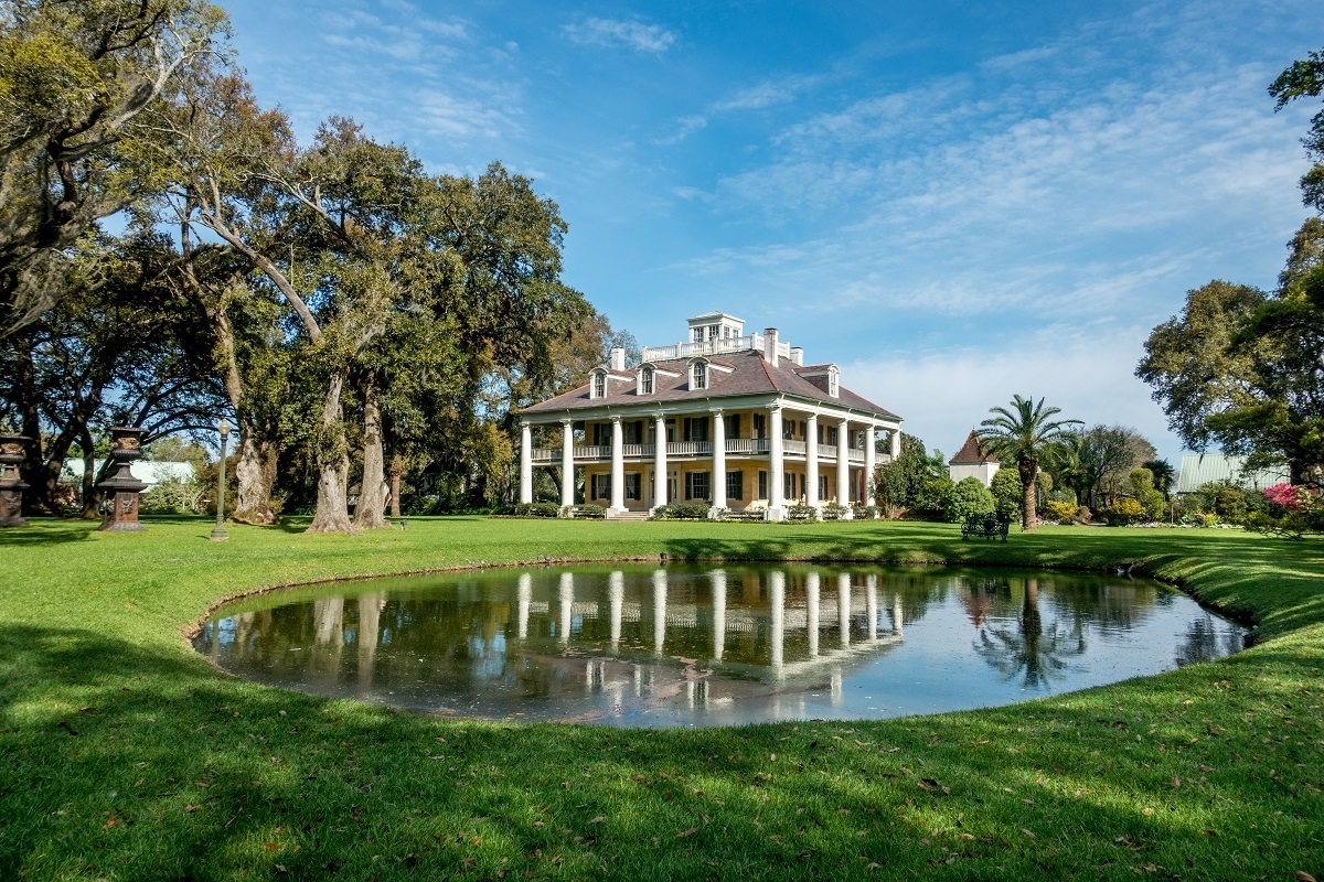 White mansion with columns and small pond