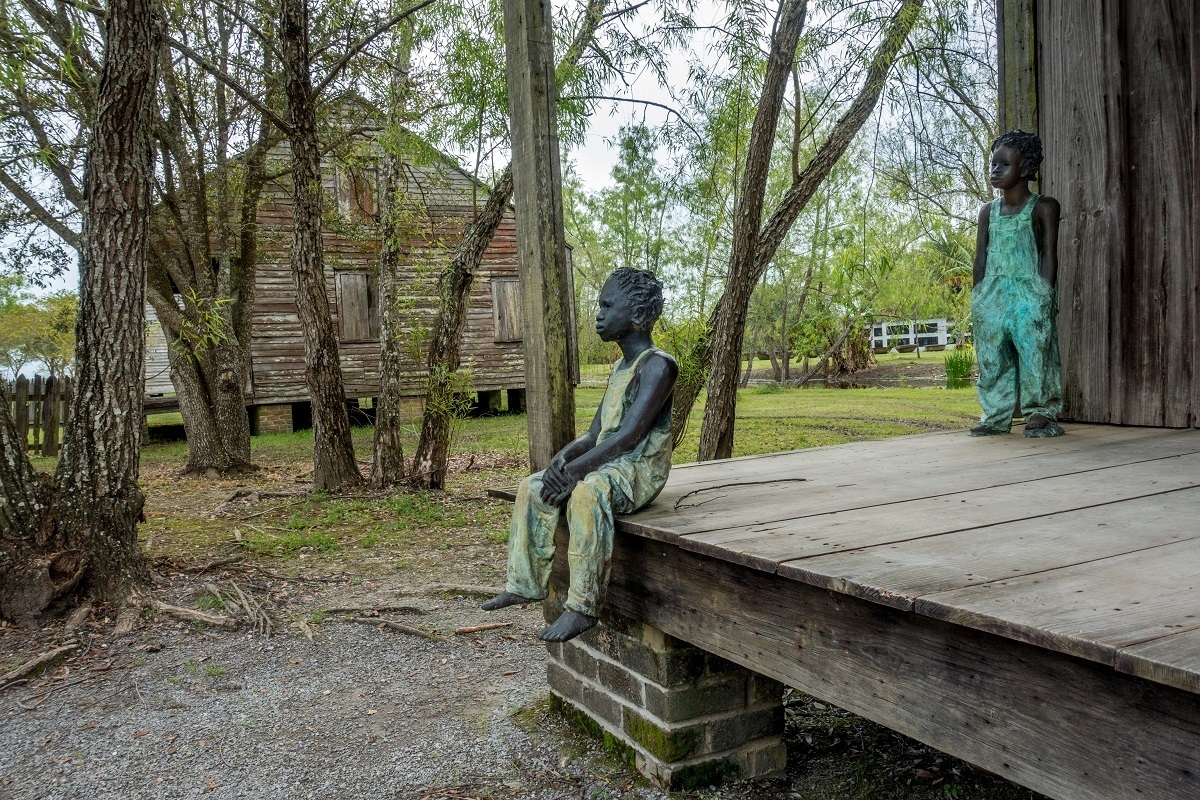 Statues representing child slaves gazing into the distance