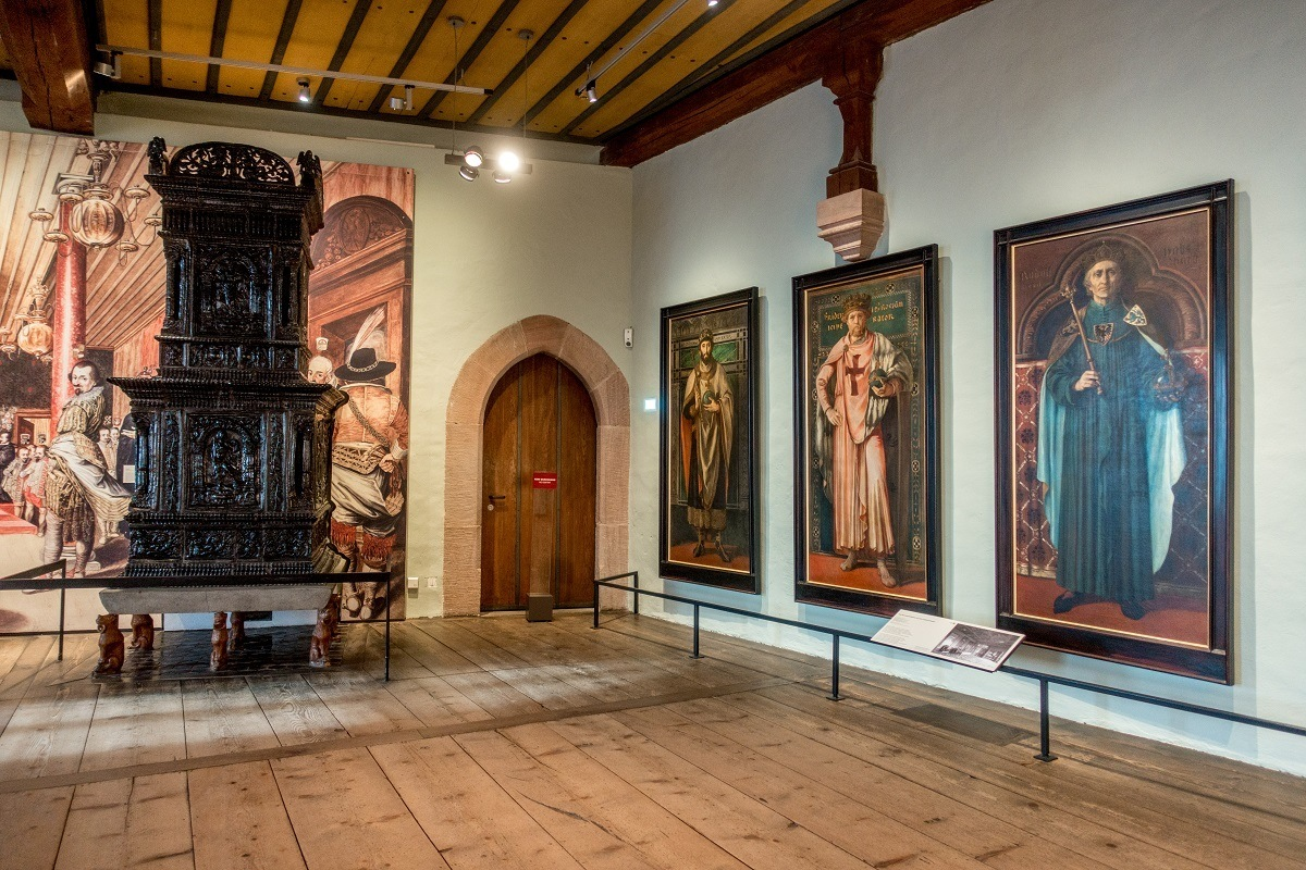 Paintings of emperors line a museum wall