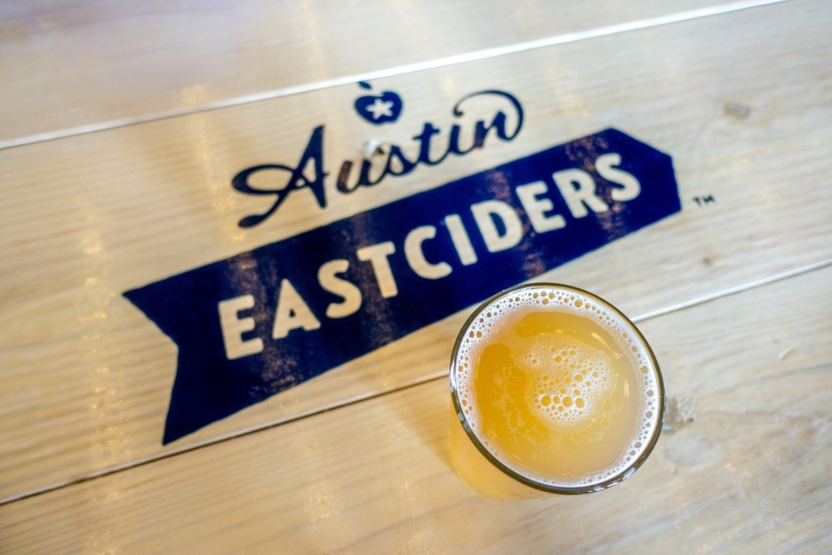 Pint of cider on table with Austin Eastciders logo