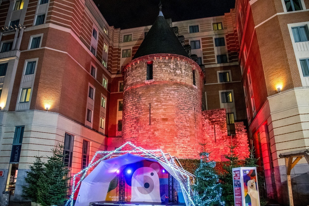 Stage in front of medieval tower surrounded by modern building