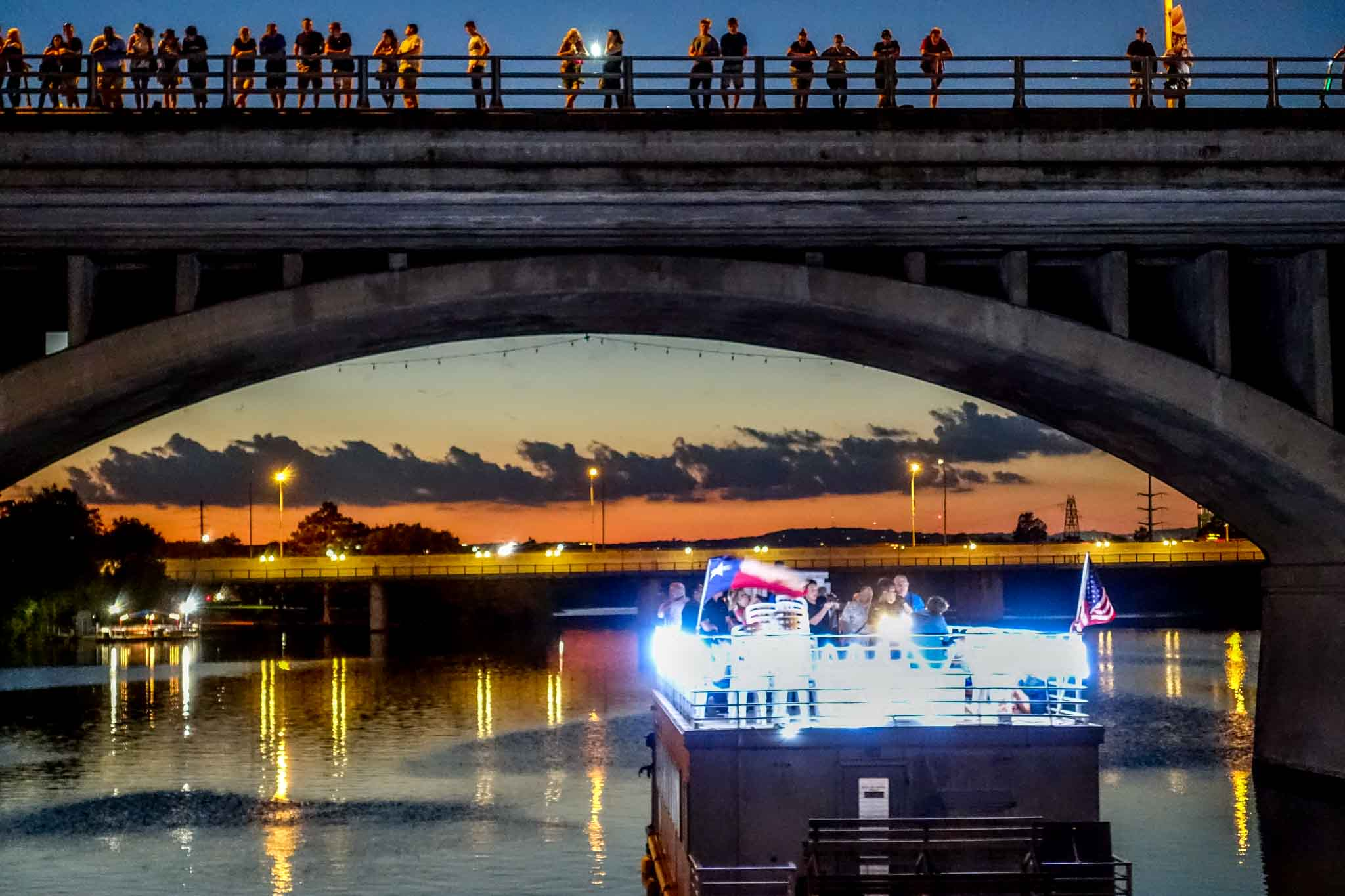 Boat under bridge with people standing above