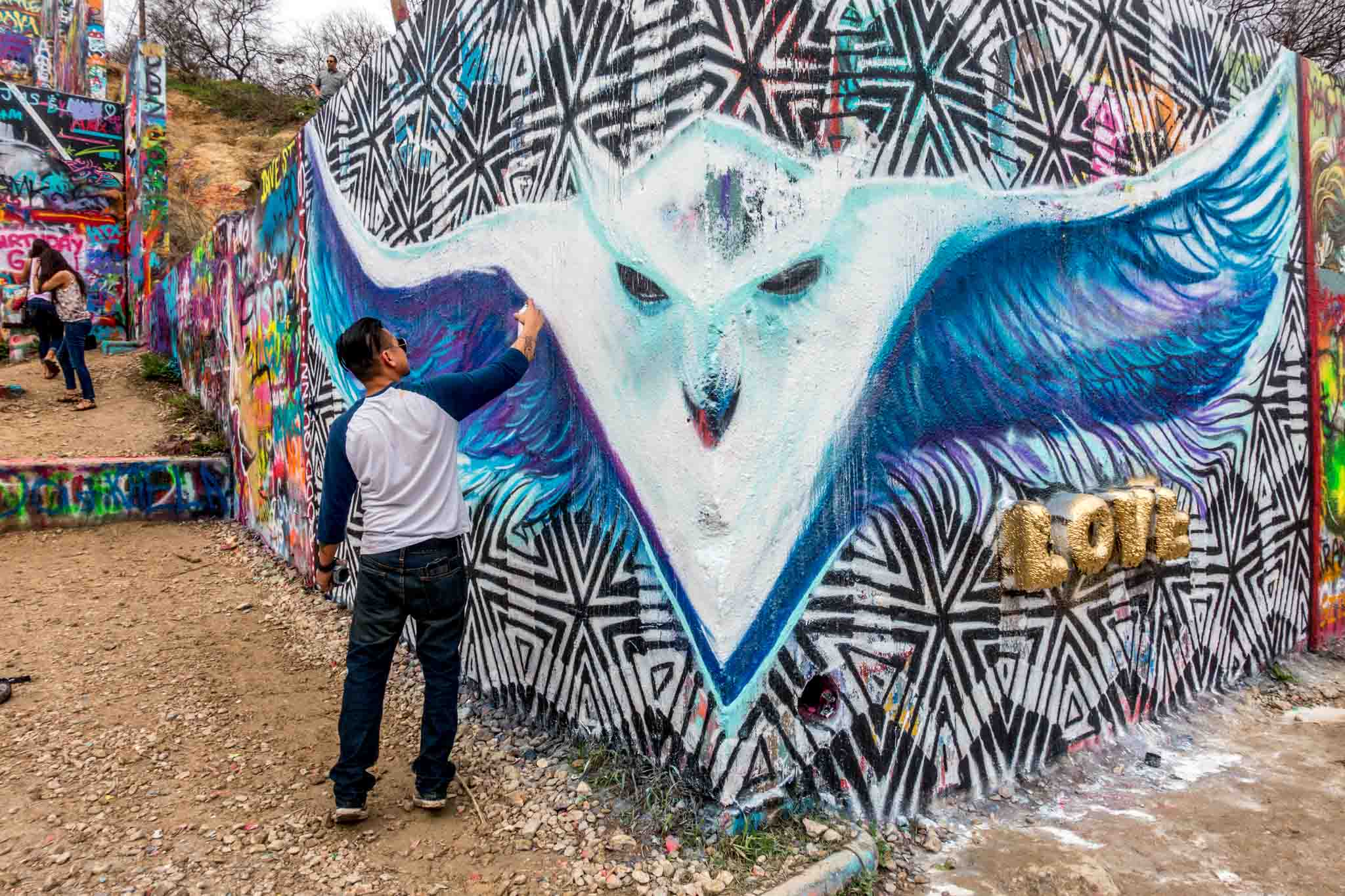 Artist spray painting a white design at HOPE Outdoor Gallery
