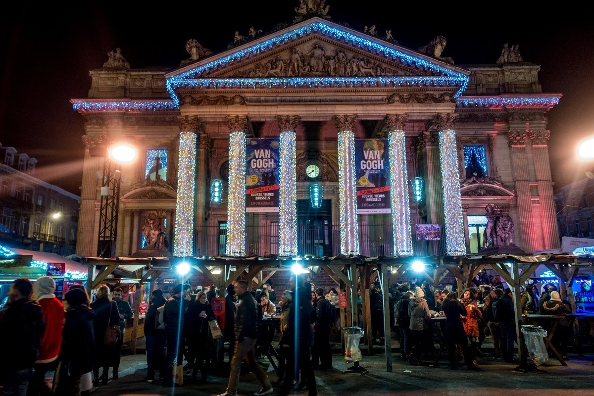 Building with columns and market stalls lit up in Brussels