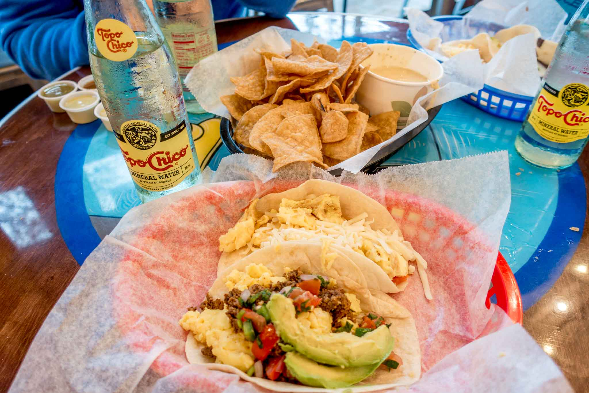 Breakfast tacos, chips, queso, and Topo Chico on a table