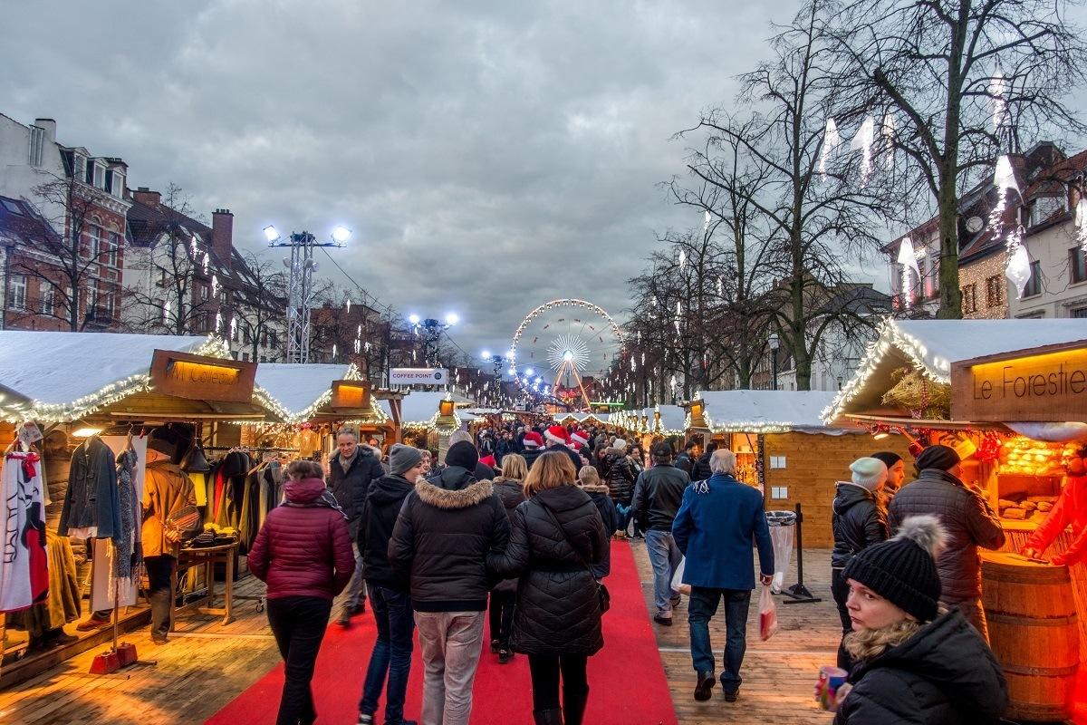 People walking through rows of Christmas market vendors