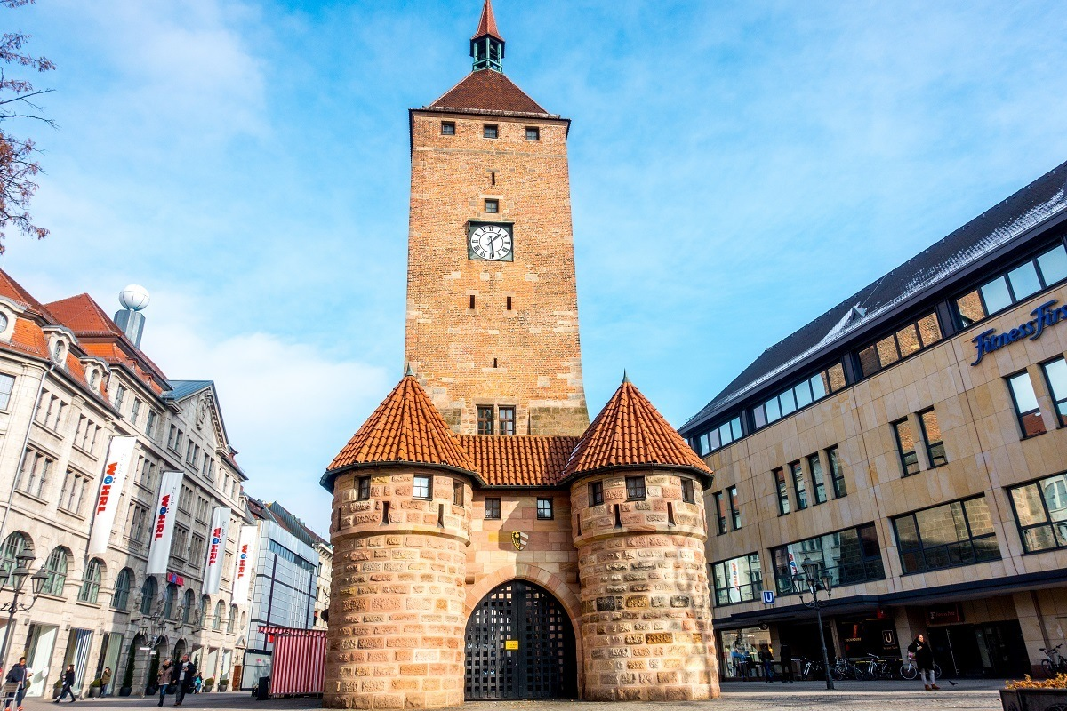 Tall brick tower with the arched city gate immediately in front of it