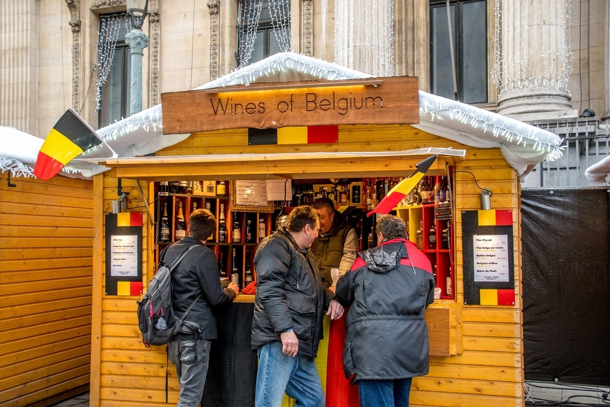 People at market stall selling wines of Belgium