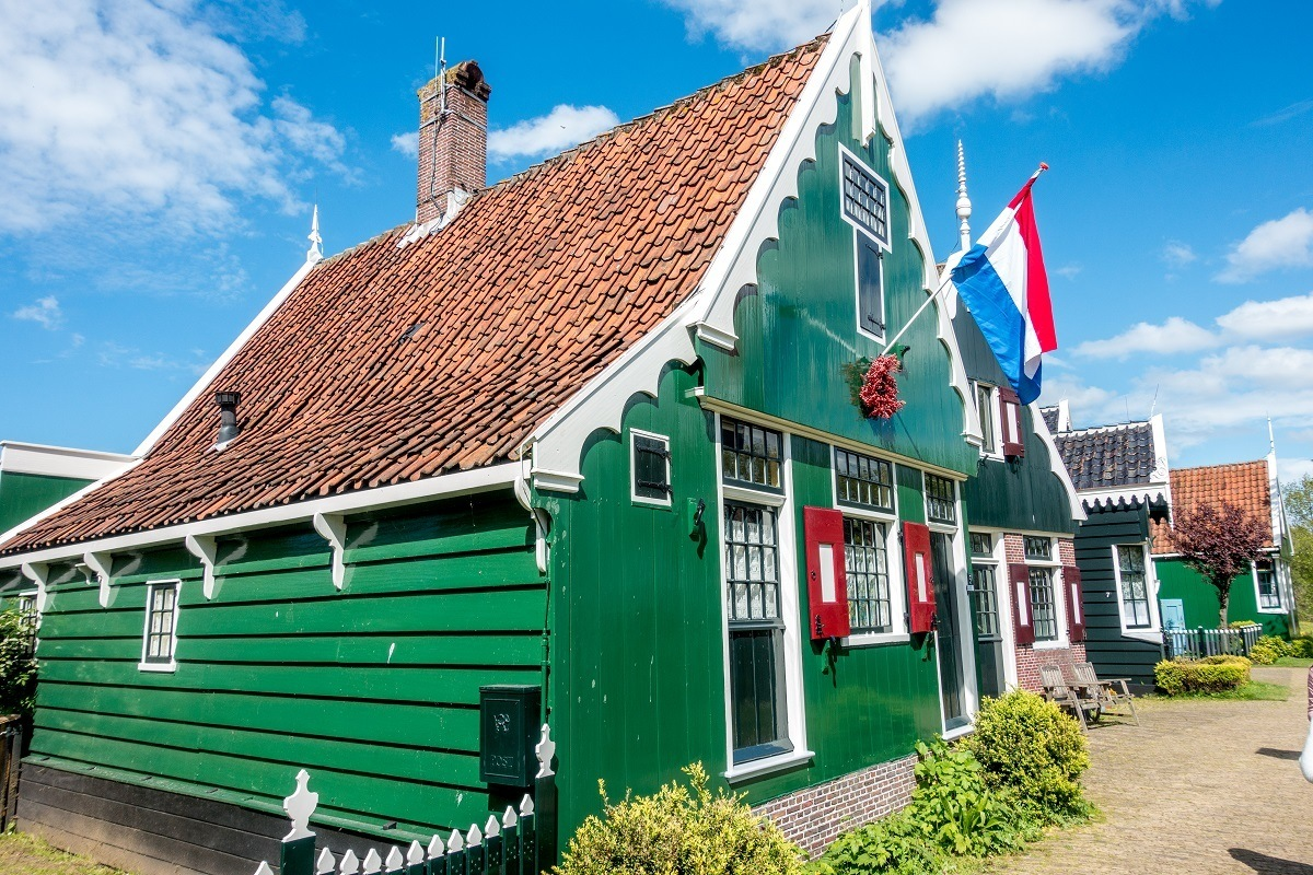 Traditional green Zaans houses flying Dutch national flag