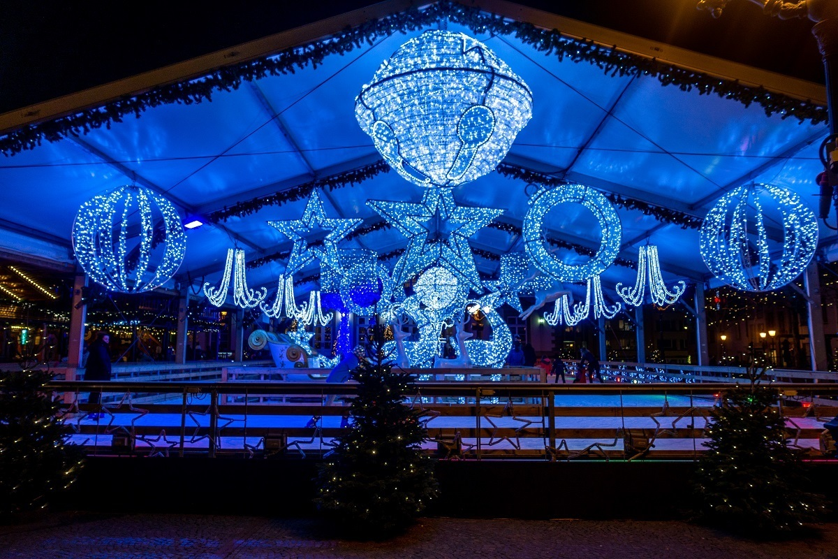 Ice skating rink trimmed with blue Christmas lights at night