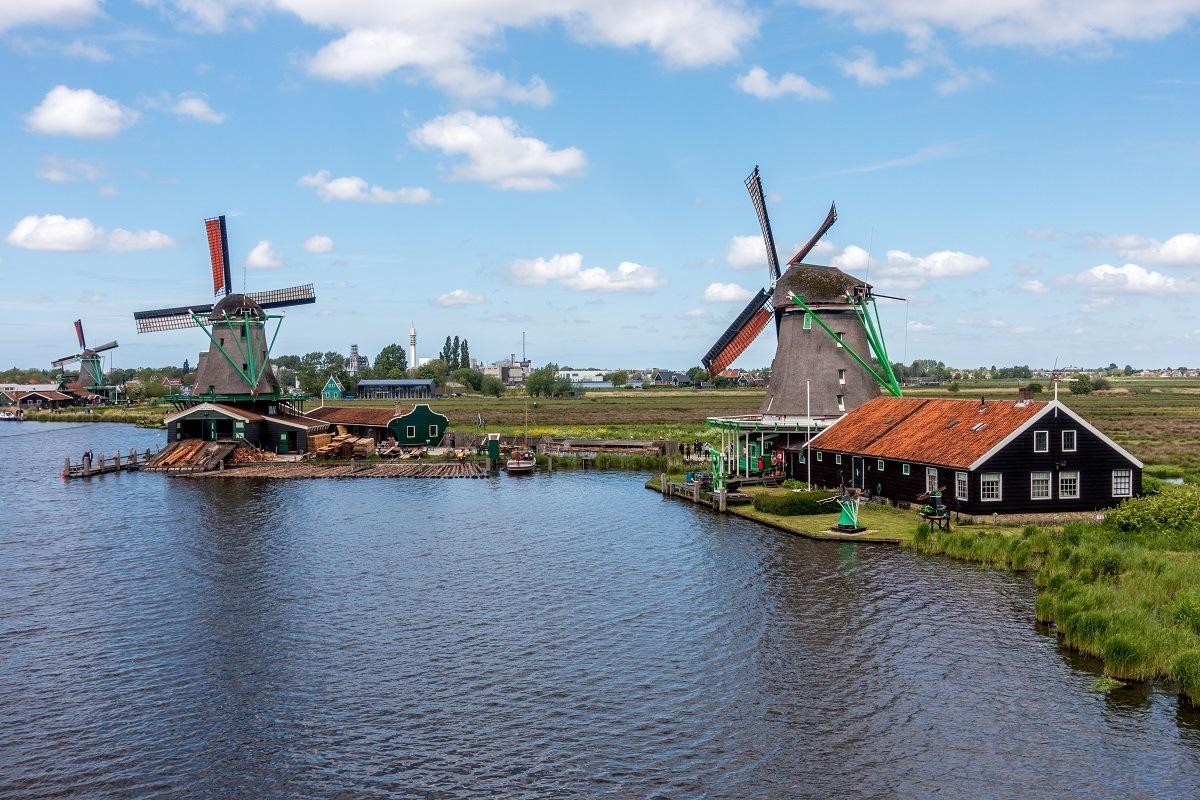 Three windmills along the water