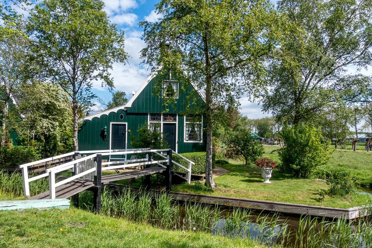 Green traditional Zaans house with a bridge over the canal