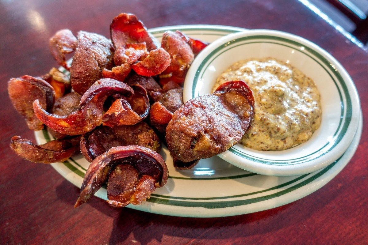 Fried andouille chips with a side of mustard