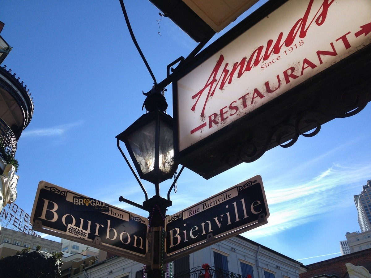 Sign for Arnaud's Restaurant beside street sign at Bourbon and Bienville