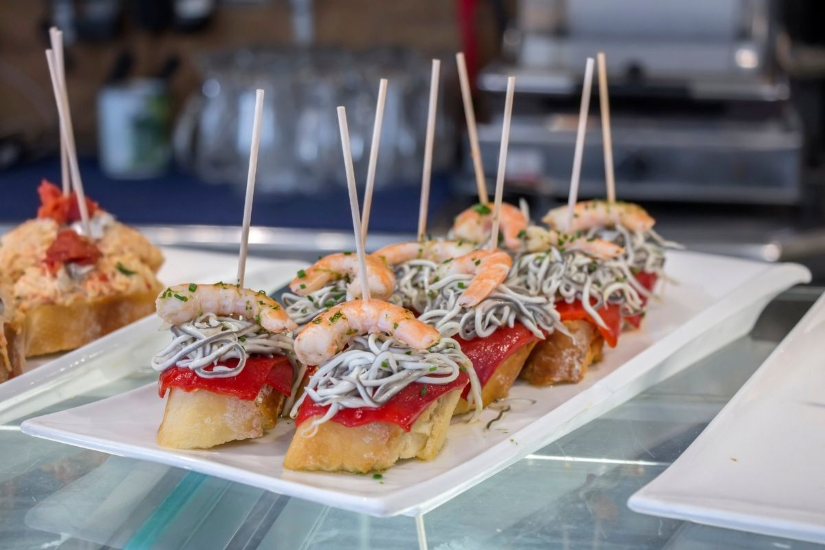 Platter filled with pintxos including shrimp, red peppers, and baby eels